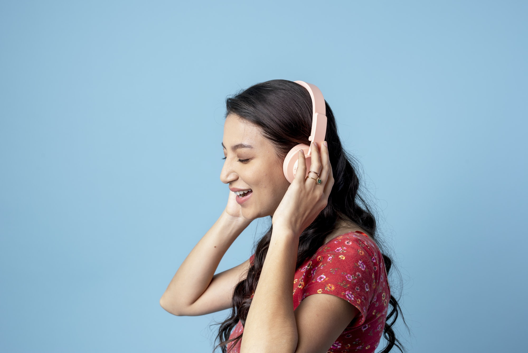 Cheerful woman listening to music with a headset on blue background